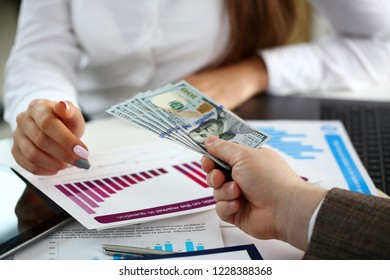 Male arm pay bunch of hundred dollars bills to office clerk closeup. Bribery accept backhander banknote venality laundering back scheme offshore company irs kickback collusion lobby gift compensation