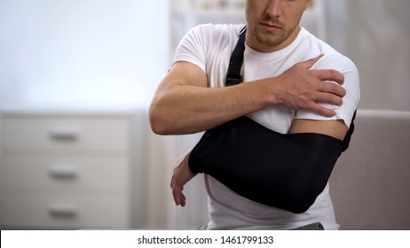 Male in arm sling suffering pain in shoulder, result of work trauma, orthopedics