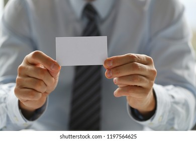 Male arm in suit give blank calling card to visitor closeup. White collar colleagues company name exchange job interview sale clerk id executive or ceo finance support formal identity concept