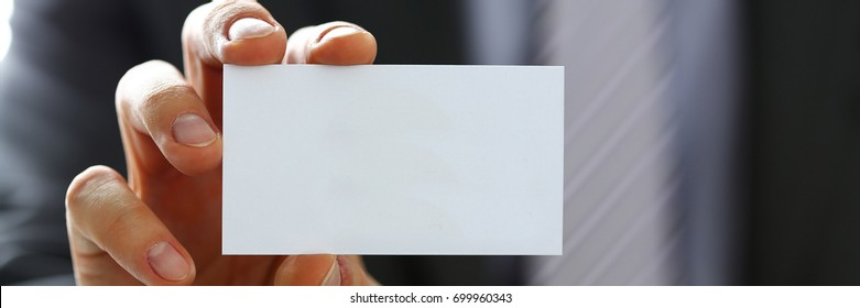 Male arm in suit give blank calling card to visitor closeup. White collar colleagues company name exchange, job interview, sale clerk id, executive or ceo, finance support, formal identity concept