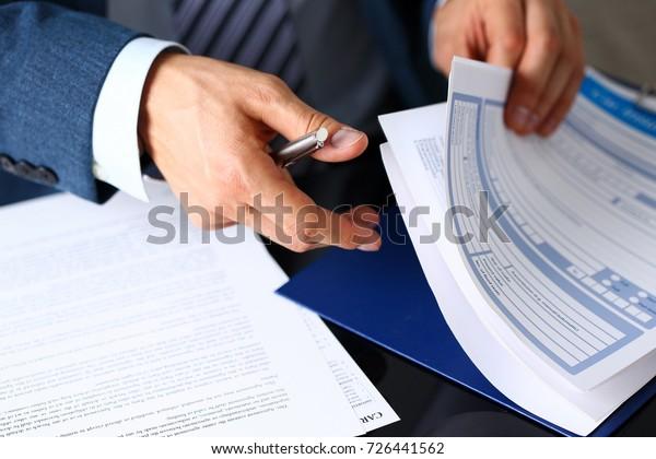Der männliche Arm in Anzug bietet Versicherungsform auf Pad geklickt und silberner Stift, um sich in der Nähe zu registrieren. Schnäppchen, Vermeidung von Geldverlust des Fahrers, sichere Straßenfahrt, ungefähre Antriebsidee, Schutzkonzept des Eigentümers