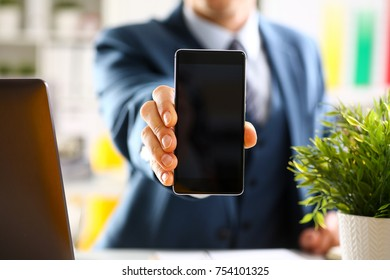 Male arm in suit show in camera phone display screen closeup. Read news mania send sms chat addict use electronic bank modern lifestyle job plan colleague share blog tweet web application search