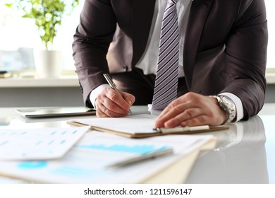 Male arm in suit and tie fill form clipped to pad with silver pen closeup. Sign gesture read pact sale agent bank job make note loan credit mortgage investment finance executive chief legal law
