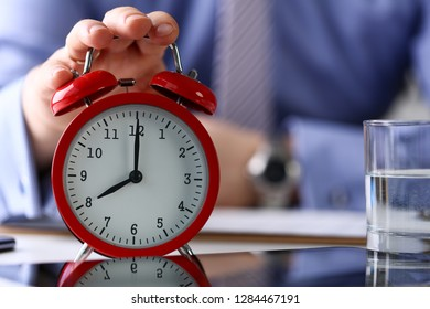 Male arm in suit and tie hold up red alarm clock in office with eight o'clock early morning closeup. Student person late for date worker job meeting AM PM concept
