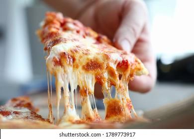 Männlicher Arm, der eine Scheibe schmackhafte frische Pizza mitnimmt, Nahaufnahme