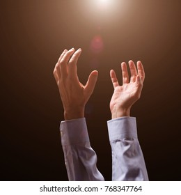 Male arms and hands raised and outstretched in the air to divine light. Man praying, begging, pleading imploring or supplicating. Black background. Businessman with Christian Catholic religious faith