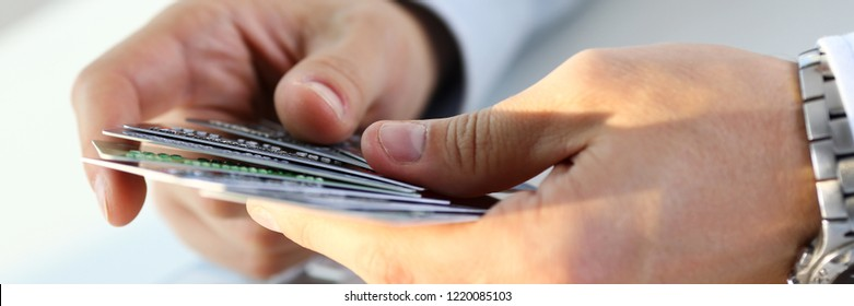 Male arms hold and count bunch of credit cards picking one closeup.