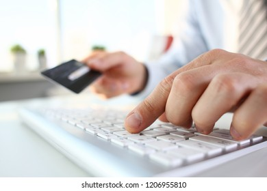 Male arms hold credit card press buttons making transfer closeup. Anti-fraud financial security when entering client discount program number or filling personal credential password login to account