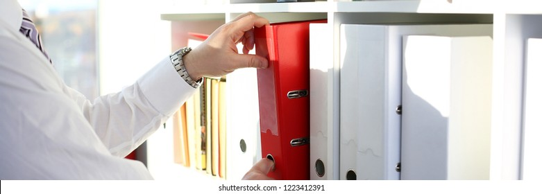 Male arms pick red file folder from office book shelf closeup. Store pile of project documentation concept