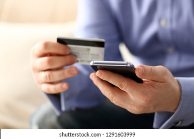 Male arms in suit hold credit card and phone make transfer closeup. Anti-fraud financial security when entering client discount program number or filling personal credential password login to account