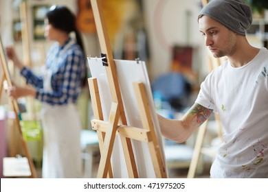 Male artist dressed in beanie hat and white shirt covered in colorful paint sketching on easel in brightly lit studio with blurred female artist in apron in background