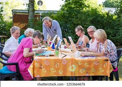 Male artist giving art lessons to the group of senior women, practicing in painting pictures sitting at one table outdoors in backyard.