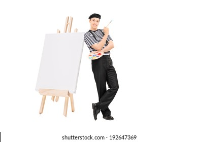 Male artist leaning on an easel and holding a paintbrush isolated on white background