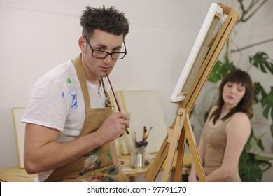 male artist painting female model at art studio