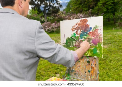 Male artist painting a standing in front of  a sketchbook during creation a beautiful sketch of picture outdoors