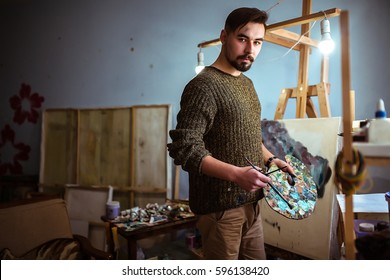 Male Artist Working On Painting In Bright Daylight Studio