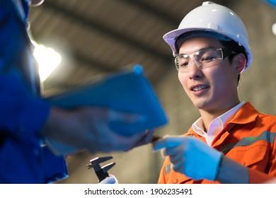 Asiatischer Ingenieurberuf, der eine Diskussion mit der Maschine in der Fabrik führt, zwei asiatische Mitarbeiter-Brainstorm, die den Prozess curcuit Mutter-Board der Maschine erklären und löst.