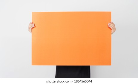 Male asian hand is holding the blank orange color paper on white background.
