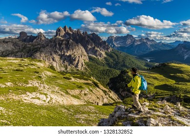Male asian hiker looking at majestic view of Dolomites mountain range in Tre Cime di Lavaredo Loop trail, Italy