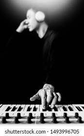 male asian musician, artist, songwriter playing keyboard synthesizer and listening music for creating new sound in his song