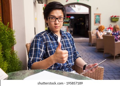 Male asian student with digital tablet. Outdoor photo