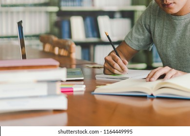 male asian student studying and reading book in library