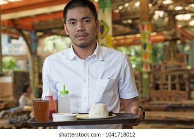 Male Asian waitercarrying food tray in a restaurant.