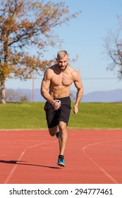 Male Athelete sprinting on a tartan athletics track on a bright sunny day