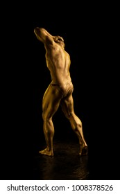 Male athlete bodybuilder in gold body paint posing on black background