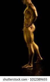 Male athlete bodybuilder in gold bodyart paint posing on black background