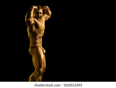 Male athlete bodybuilder in gold paint posing on black background