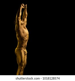 Male athlete bodybuilder in golden bodyart posing on black background