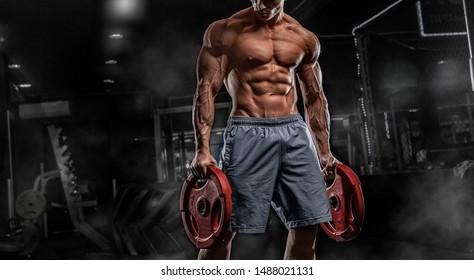 Male athlete bodybuilder posing on a black background