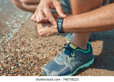 male athlete checking step count in smart wristband at the seashore in summer
