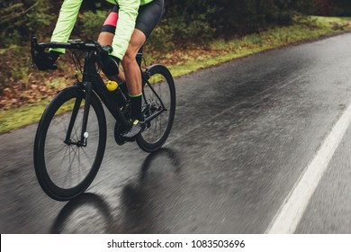 Male athlete in cycling gear riding bike on wet road. Low section shot of cyclist training outdoors on a rainy day.