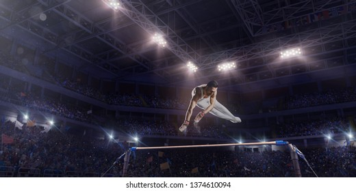 Male athlete doing a complicated exciting trick on horizontal gymnastics bars in a professional gym. Man perform stunt in bright sports clothes