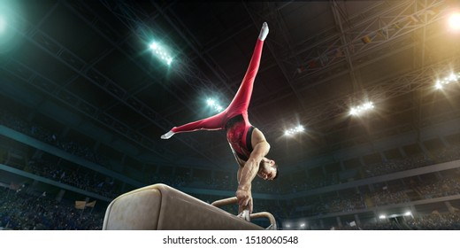 Male athlete doing a complicated exciting trick on a Pommel horse in a professional gym. Man perform stunt in bright sports clothes