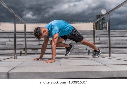 Male athlete doing leg warms before fitness workout workout, jogging in summer morning in city. Sportswear Sneakers Shorts. Active lifestyle of youth. In focus, raise your legs to press
