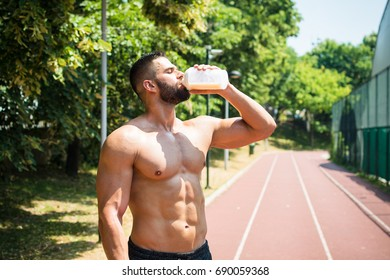 Male athlete drinking protein shake at racing track