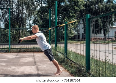 A male athlete is engaged in the open air loops, push-ups at the fence. In summer, in shorts and a white T-shirt.