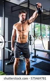 Male athlete exercising with kettlebells in gym