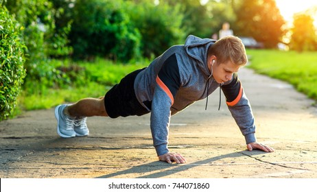 Male athlete exercising in park. Portrait of a male guy doing push-ups. The concept of a healthy lifestyle. Strength and motivation