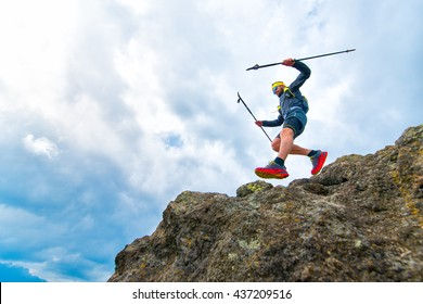 Male athlete falls over a cliff with sticks while practical training at the mountain trail