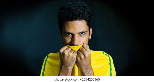 Male athlete or fan kissing yellow uniform on black background
