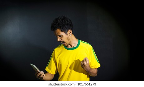 Male athlete or fan in yellow uniform looking cell phone on black background