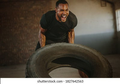 Male athlete flipping heavy tire inside an abandoned warehouse. Strong man flipping a tyre during an intense training session in a cross workout space.