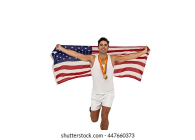Male athlete with gold medals around his neck running with american flag on white background