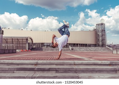 Male athlete, guy dancer summer city. Standing one arm jump. Fashionable modern break dance style fast, fitness sport hip hop motion. Urban culture street dance. Acrobatic exercises. In t-shirt jeans