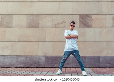 Male athlete, guy dancer in summer city. Free space for motivation text. Fashionable modern break dance style, fitness sport hip hop. Urban culture, street dance. In a t-shirt jeans and sneakers