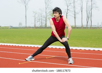 Male athlete in his fifthies is stretching on an athletics track - Baarn, the Netherlands